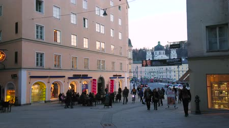 crowded : SALZBURG, AUSTRIA - FEBRUARY 27, 2019: The shopping street of Linzergasse with high edifices of  Neustadt district and crowds of people, on February 27 in Salzburg Stock Footage