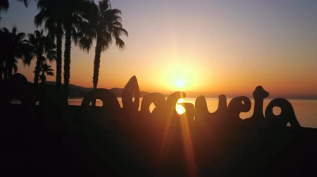 waterkant : MALAGA, SPAIN - SEPTEMBER 29, 2019: The silhouette of Malagueta beach sign, palms and Mediterranean coast in bright rays of sunrise, on September 29 in Malaga