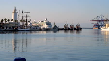 relaks : The early morning in port with a view on crystal clear water surface, La Farola lighthouse, yachts and ships, Malaga, Costa Del Sol, Spain