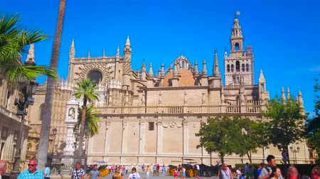 mudejar : SEVILLE, SPAIN - OCTOBER 1, 2019: The crowded historical Plaza del Triunfo square, tourists walk along the high walls of Gothic Cathedral, on October 1 in Seville Stock Footage