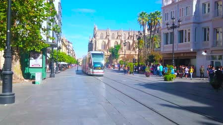 manor : SEVILLE, SPAIN - OCTOBER 1, 2019: The vibrant life in old town; the modern tram rides the Constitution avenue, where the crowds of tourists walk along historical edifices, on October 1 in Seville
