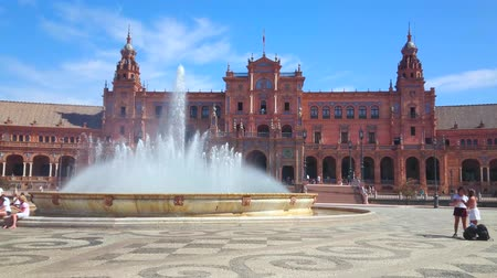 iberian : SEVILLE, SPAIN - OCTOBER 1, 2019: The large fountain in the middle of Plaza de Espana is the most beloved place for relaxing under the refreshing sprays, on October 1 in Seville