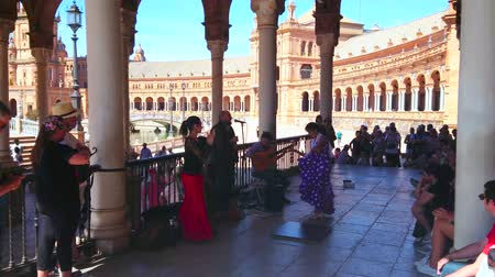 mudejar : SEVILLE, SPAIN - OCTOBER 1, 2019:Spanish dancer performs emotional flamenco with elements of tap dance in accompaniment of the music band in gallery of Plaza de Espana, October 1 in Seville