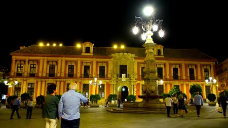 mudejar : SEVILLE, SPAIN - OCTOBER 1, 2019: Historical Archbishops Palace in Plaza Virgen de los Reyes square with scenic lamppost fountain in bright evening illumination, on October 1 in Seville