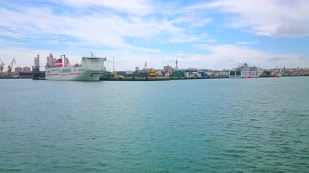 waterkant : CADIZ, SPANJE - SEPTEMBER 21, 2019: De zeecontainers en het vrachtschip in de haven van Cadiz met uitzicht op talrijke vrachtkranen op de achtergrond, op 21 september in Cadiz