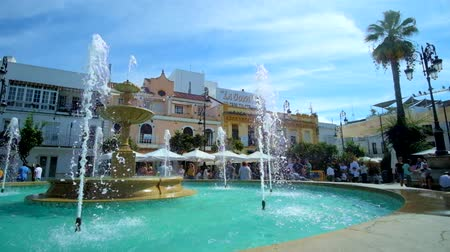 triângulo : SANLUCAR, SPAIN - SEPTEMBER 22, 2019: Refreshing jets of the old fountain in Plaza del Cabildo square attract people to spend time here, on September 22 in Sanlucar