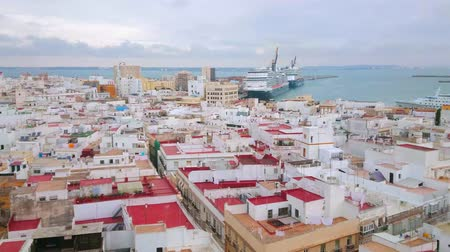 residencial : CADIZ, SPAIN - SEPTEMBER 21, 2019: Panorama from the bell tower of Cathedral with a view on city roofs, port, cruise liners, cargo ships, cranes and historical landmarks, on September 21 in Cadiz