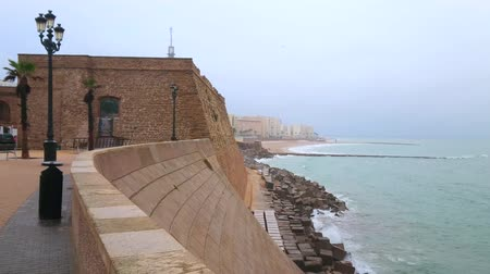 The rainy morning on Atlantic Ocean shore with a view on Baluarte de San Roque (bastion) of Cadiz fortress, foggy rainy sky and stormy waters, Spain