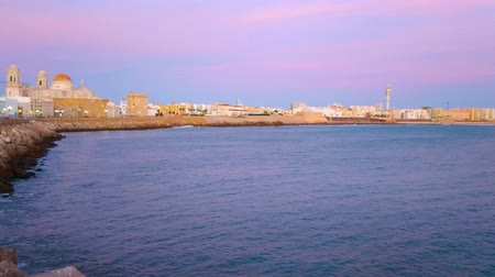 crepúsculo : Enjoy romantic dusk from the shore of Atlantic Ocean with a view on skyline of Cadiz, Spain