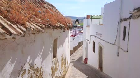 residencial : ARCOS, SPAIN - SEPTEMBER 23, 2019: The descent through the narrow curved alley of pueblo blanco (white town), located on the mountain slopes, on September 23 in Arcos