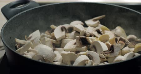 cooktop : Close up of delicious sliced ??button mushrooms being stir-fried fried with onion and oil on the pan