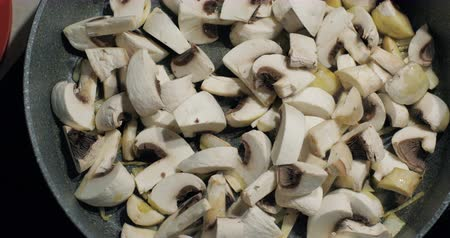 cooktop : Close up of delicious sliced ??button mushrooms being stir-fried with fried onion on the pan