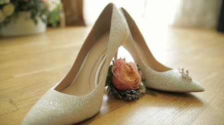 casamento : Wedding bouquet placed in between brides wedding shoes Stock Footage