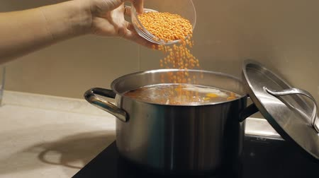 cooktop : Add lentils to boiling soup with chicken, carrots and potatoes. Slow motion
