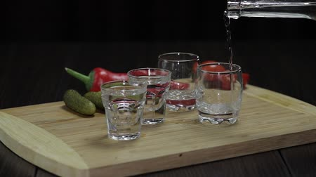 ginástico : Pour vodka from a bottle into three glasses. The glasses are placed on a wooden board with pepper, marinated cucumbers and cherry tomatoes
