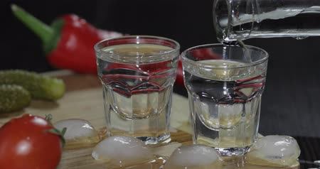 hortelã pimenta : Pour vodka from a bottle into shot glasses which are placed on a wooden board with pepper, marinated cucumbers and cherry tomatoes. Man takes a glass with vodka