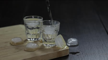 klín : Pour vodka from a bottle into shot glasses with ice cubes. Slow motion