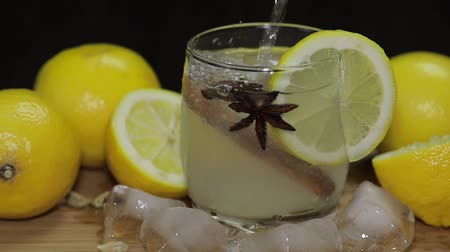 tomilho : Pours lemon juice into glass with ice, thyme and lemon slices, slow motion. Lemon cocktail with thyme and ice on black background. Refreshing alcoholic cocktail drink.