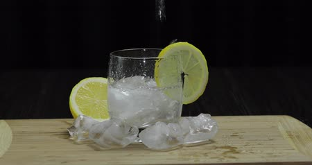 tonik : Pours lemon juice into glass with ice, thyme and lemon slices. Lemon cocktail with thyme and ice on black background. Refreshing alcoholic cocktail drink.