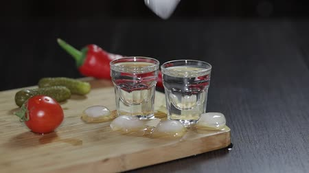 tonik : Vodka in shot glasses which are placed on a wooden board with pepper, marinated cucumbers and cherry tomatoes.. Adding ice cubes. Black background Stok Video