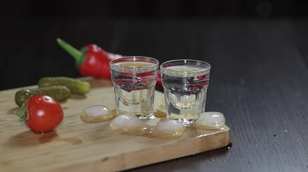 alkoholik : Vodka in shot glasses which are placed on a wooden board with pepper, marinated cucumbers and cherry tomatoes.. Adding ice cubes. Black background Dostupné videozáznamy