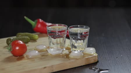 klín : Vodka in shot glasses which are placed on a wooden board with pepper, marinated cucumbers and cherry tomatoes.. Adding ice cubes. Black background Dostupné videozáznamy