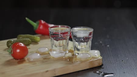 biber : Vodka in shot glasses which are placed on a wooden board with pepper, marinated cucumbers and cherry tomatoes.. Adding ice cubes. Black background Stok Video