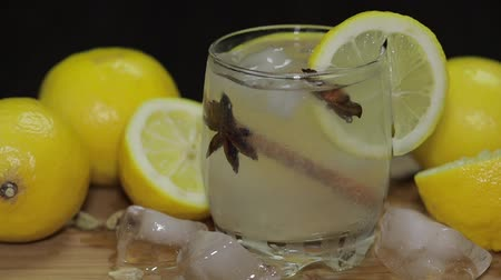 lemoniada : Refreshing alcoholic cocktail drink on rustic wood board. Adding ice cubes.