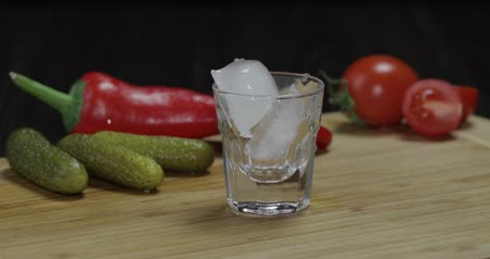 hortelã pimenta : A man puts a glass then fills it with vodka and picks up a glass. Wooden board with pepper, marinated cucumbers and cherry tomatoes.