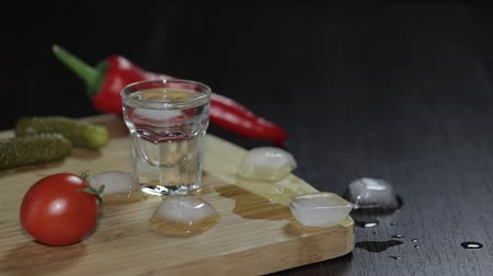 klín : Man puts a glass filled with vodka on the wooden board with pepper, marinated cucumbers and cherry tomatoes.