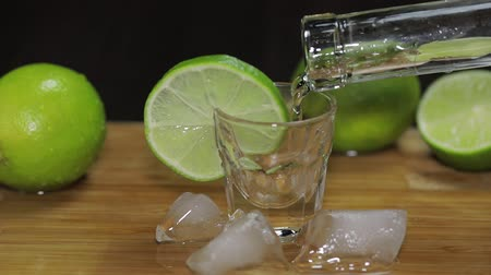 tonik : Man puts a glass then fills it with vodka or tequila and picks up a glass. Wooden board with lime fruit Stok Video
