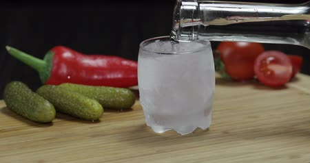 маринованный : A man puts icy glass then fills it with vodka and picks up a glass. Wooden board with pepper, marinated cucumbers and cherry tomatoes.