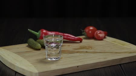 охлажденный : Man takes a glass filled with vodka from the wooden board with pepper, marinated cucumbers and cherry tomatoes