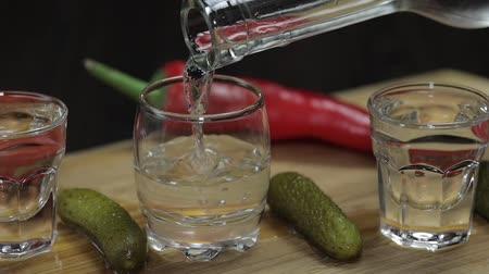 klín : Pouring vodka into shot glasses which are placed on a wooden board with pepper, marinated cucumbers and cherry tomatoes. Slow motion