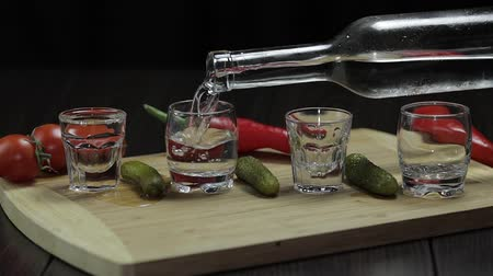 hortelã pimenta : Pouring vodka into shot glasses which are placed on a wooden board with pepper, marinated cucumbers and cherry tomatoes. Slow motion