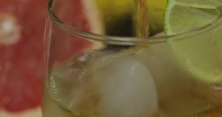 pálinka : Pour liquor from a bottle into a glass cup with ice cubes. Close-up shot. Fresh fruits in the background. Lime Grapefruit. Prepare a cocktail of whiskey, cognac or liqueur.