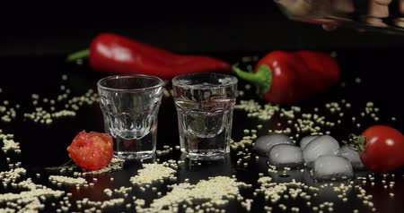 ginástico : Pouring vodka into shot glasses which are placed on a black surface with pepper, sesame and cherry tomatoes.