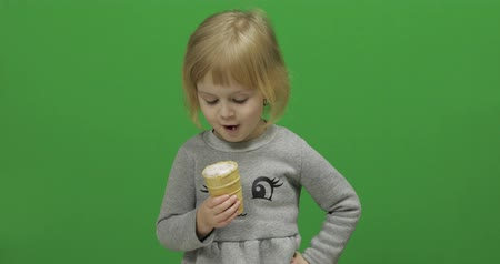 little : Kid girl eat ice cream on a Green Screen, Chroma Key. Happy three years old girl. Cute girl smiling. Pretty little child, 3-4 year old blonde girl. Make faces