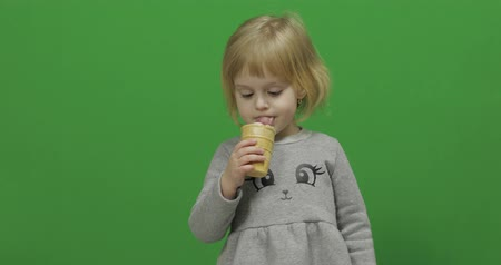 tevreden : Kid girl eat ice cream on a Green Screen, Chroma Key. Happy three years old girl. Cute girl smiling. Pretty little child, 3-4 year old blonde girl. Make faces