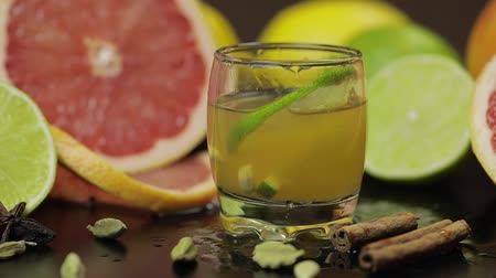 pálinka : Lime slice falls into a glass cup with an alcoholic cocktail. Fresh fruits in the background. Lime Grapefruit. Prepare a cocktail of whiskey, cognac or liqueur. Slow motion Stock mozgókép