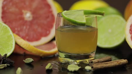 бурбон : Lime slice falls near a glass with an alcoholic cocktail. Fresh fruits in the background. Lime Grapefruit. Prepare a cocktail of whiskey, cognac or liqueur. Slow motion
