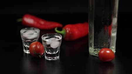 hortelã pimenta : Cherry tomato roll up to two cups of vodka near bottle with vodka. On the black background there are two red peppers. Alcohol bar