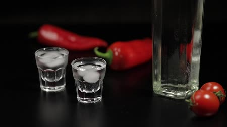 охлажденный : Cherry tomato roll up to two cups of vodka near bottle with vodka. On the black background there are two red peppers. Alcohol bar