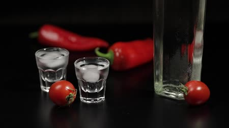 tonik : Cherry tomato roll up to two cups of vodka near bottle with vodka. On the black background there are two red peppers. Alcohol bar