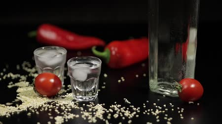 menta : Sparse sesame seeds to two cups of vodka near bottle with vodka. On the black background there are two red peppers. Alcohol bar