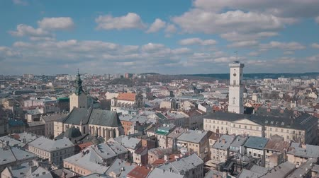 kelet európa : Lviv, Ukraine. March 20, 2019: Aerial Roofs and streets Old City Lviv, Ukraine. Central part of old city. European City. Popular areas. Panorama of the ancient town. Rooftops. Town Hall Stock mozgókép