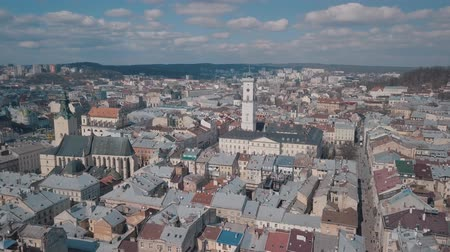 városháza : Lviv, Ukraine. March 20, 2019: Aerial Roofs and streets Old City Lviv, Ukraine. Central part of old city. European City. Popular areas. Panorama of the ancient town. Rooftops. Town Hall Stock mozgókép