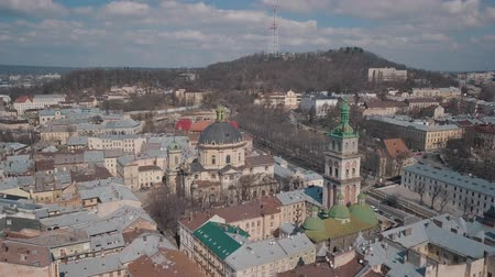 kelet európa : Lviv, Ukraine. March 20, 2019: Aerial Roofs and streets Old City Lviv, Ukraine. Central part of old city. European City. Popular areas. Panorama of the ancient town. Rooftops. Dominican Church