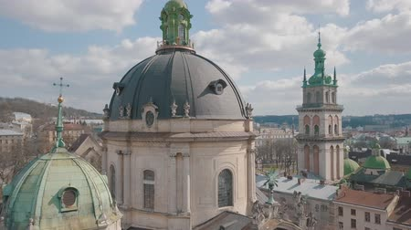 kelet európa : Lviv, Ukraine. March 20, 2019: Aerial Roofs and streets Old City Lviv, Ukraine. Dominican Church. Central part of old city. European City. Popular areas. Panorama of the ancient town. Rooftops