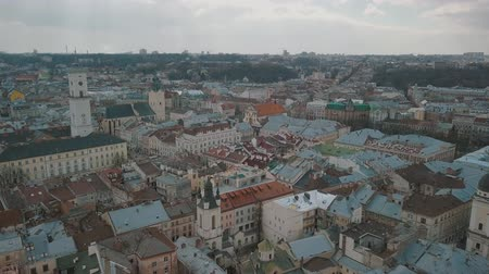 guildhall : Lviv, Ukraine. March 20, 2019: Aerial Roofs and streets Old City Lviv, Ukraine. Central part of old city. European City. Popular areas. Panorama of the ancient town. Rooftops. Town Hall Stock Footage